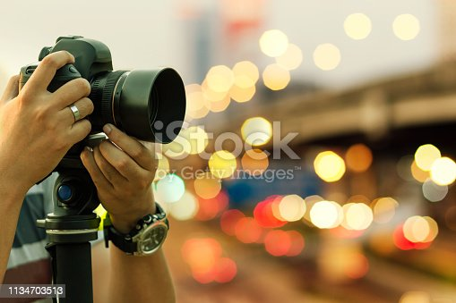 istock Photographer shooting outdoors on night light, retro toned image with selective focus on hand holding camera. 1134703513
