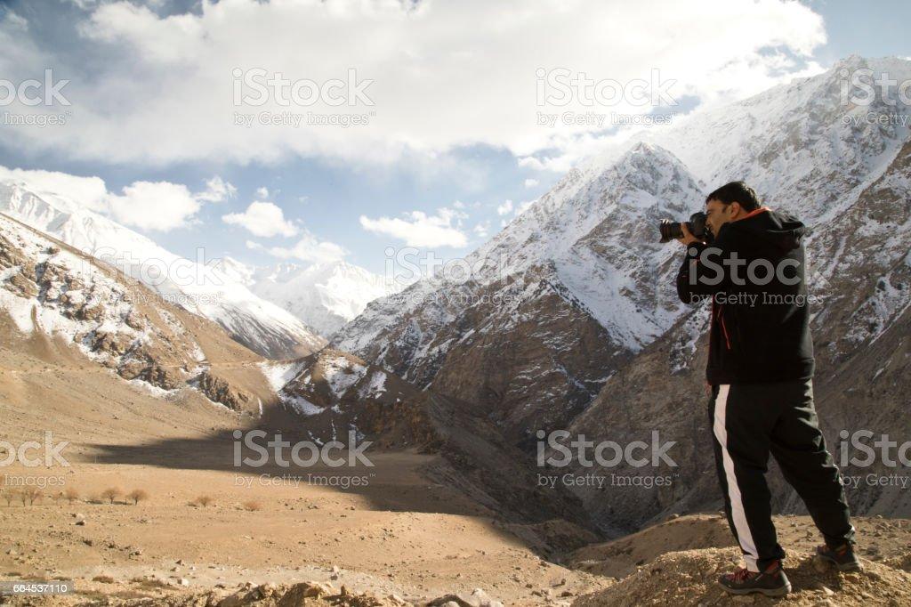Photographer shooting snowcapped Himalayan mountain royalty-free stock photo