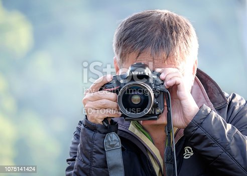 TAIWAN, HUALIEN - DECMEBER 2014 :Portrait of a photographer covering his face with the camera.