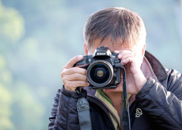 A photographer shooting with DSLR camera stock photo