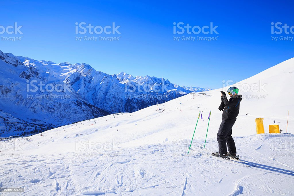 Photographer Snow skier  photographing enjoying in Winter snow mountain landscape stock photo