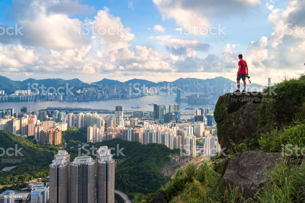 photographer standing on the top of Cliff above Hong kong cityscape stock photo