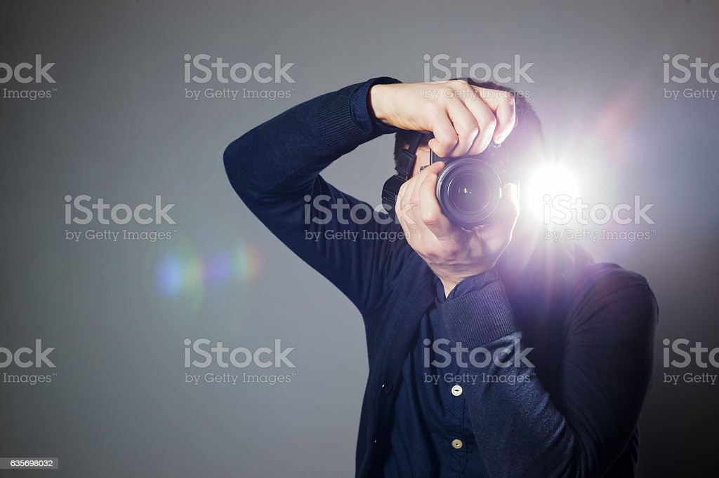 Photographer takes picture in studio using flash stock photo