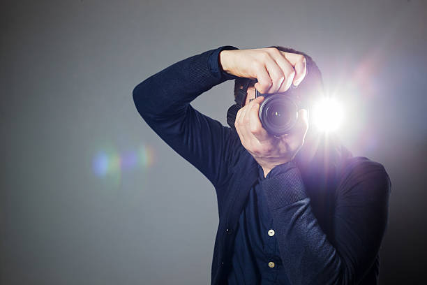 photographer takes picture in studio using flash - flash stock photos and pictures