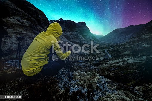 Photographer taking a picture of the northern lights in Glencoe Valley, Scotland.
