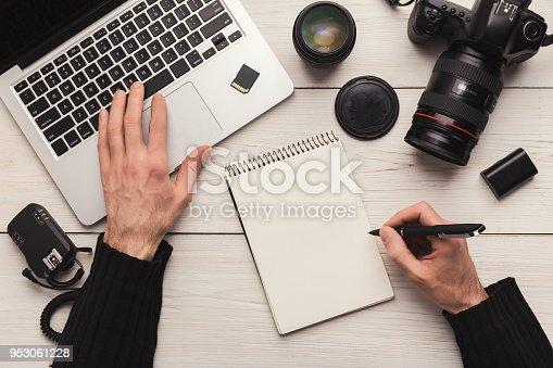 istock Photographer taking notes while using laptop 953061228
