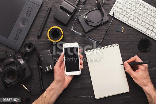 923634538 istock photo Photographer taking notes while using smartphone 958871624