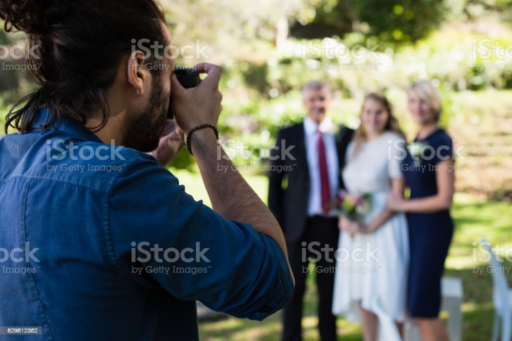 Photographer taking photo of bride and her parents stock photo