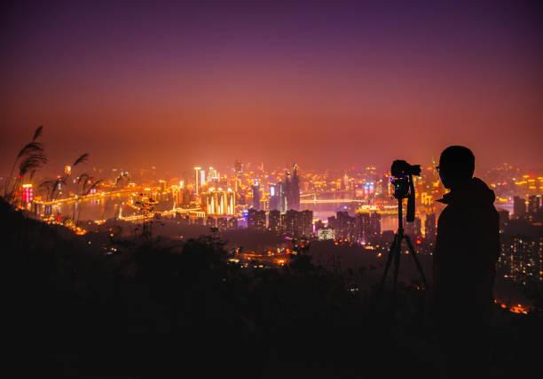 Photographer taking photos of Chongqing cityscape at night stock photo