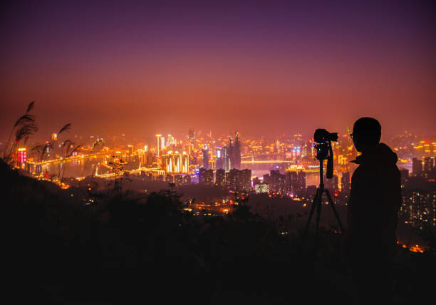 Photographer taking photos of Chongqing cityscape at night stock photo
