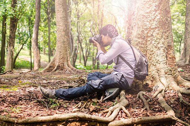 Photographer taking photos sitting under a big tree stock photo