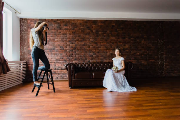 Photographer taking pictures the bride in the studio on a large leather sofa stock photo