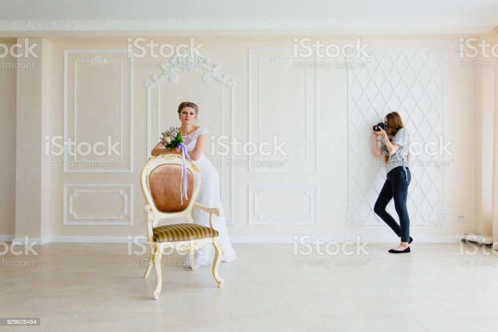 Photographer Taking Pictures The Young Sexy Bride In Studio Near Chair Royalty Free