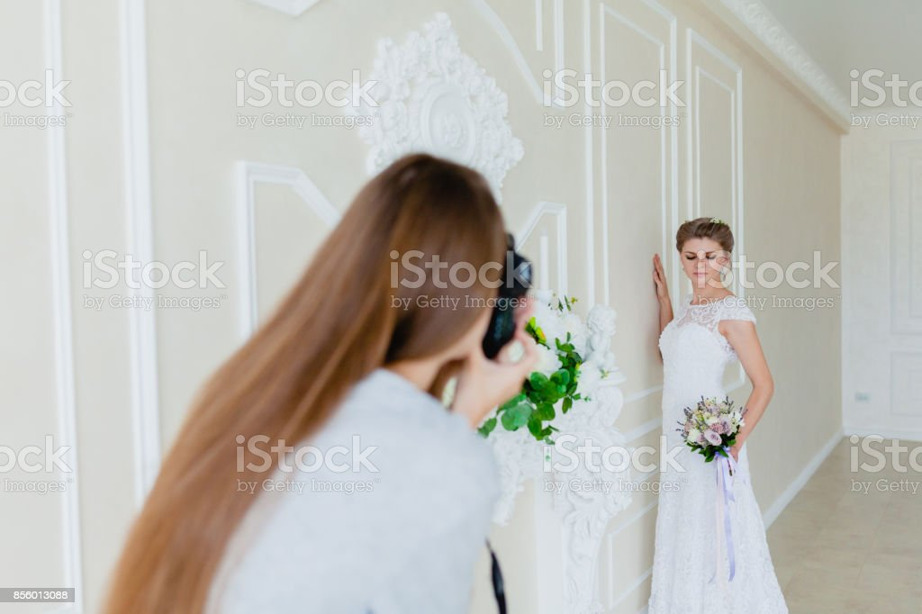 Photographer taking pictures the young sexy bride in the studio stock photo