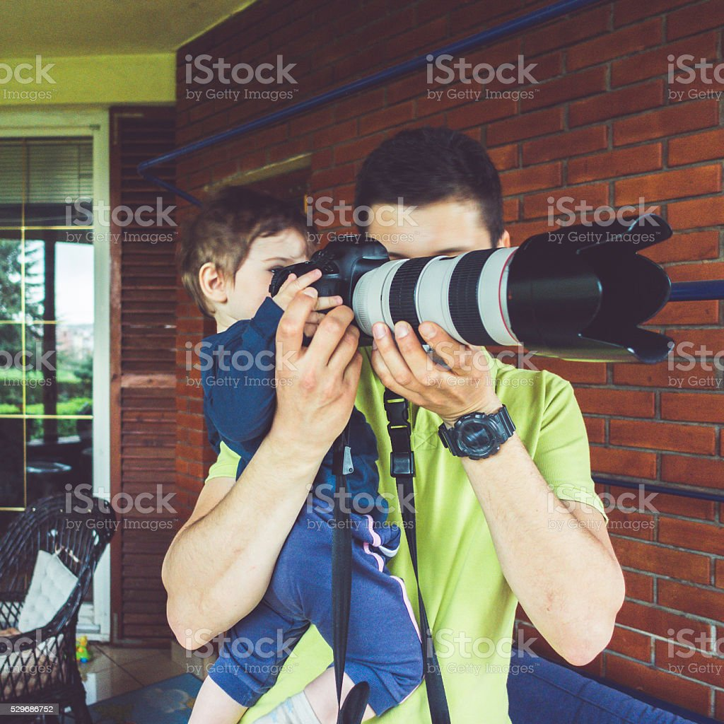 Photographer teaching his son how to use camera stock photo