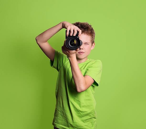 Photographer. Teenage boy using professional camera, isolated on green background. – Foto