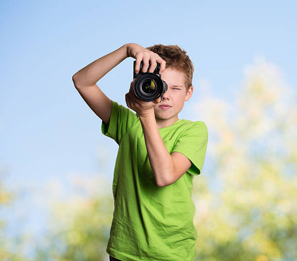 Photographer. Teenage boy using professional camera outdoors. – Foto