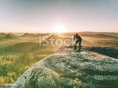 Photographer or videographer traveler with professional photo equipment is preparing for art work.  Man set heavy tripod with camera on cliff edge. Artist in pure nature.