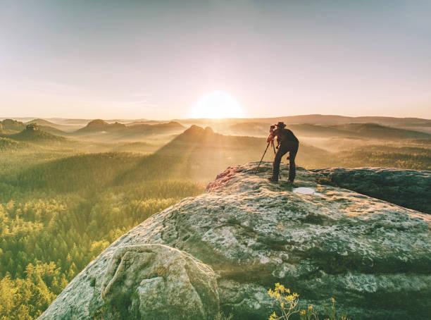 Photographer traveler with professional photo equipment works stock photo
