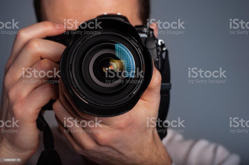 Photographer using DSLR camera in studio