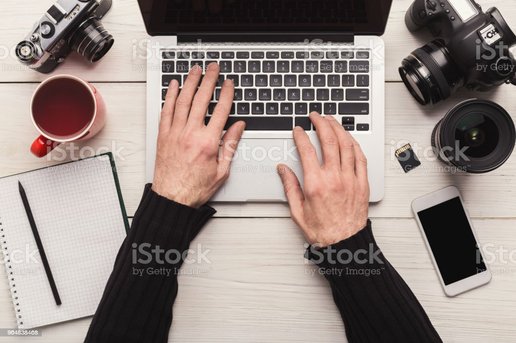 Photographer using laptop on workplace royalty-free stock photo