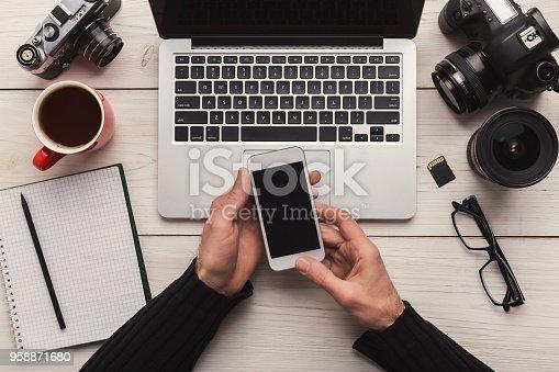 istock Photographer using smartphone on workplace 958871680