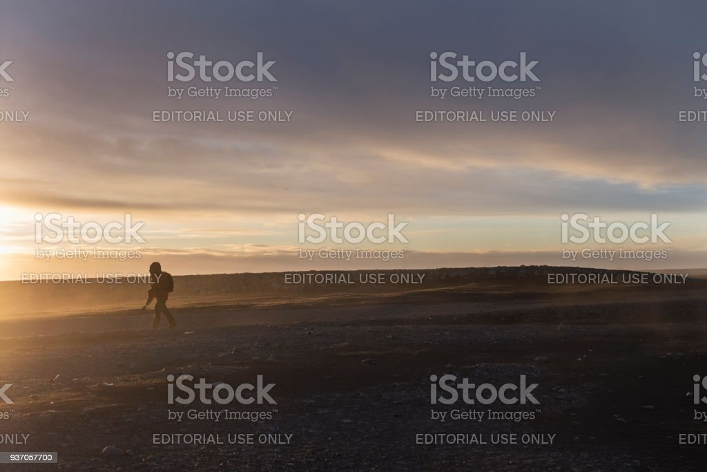 photographer walk on diamond black sand beach Iceland in morning with dramatic sky in backgrounds. stock photo