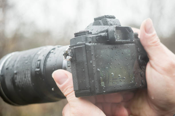 A photographer with a camera in the rain stock photo