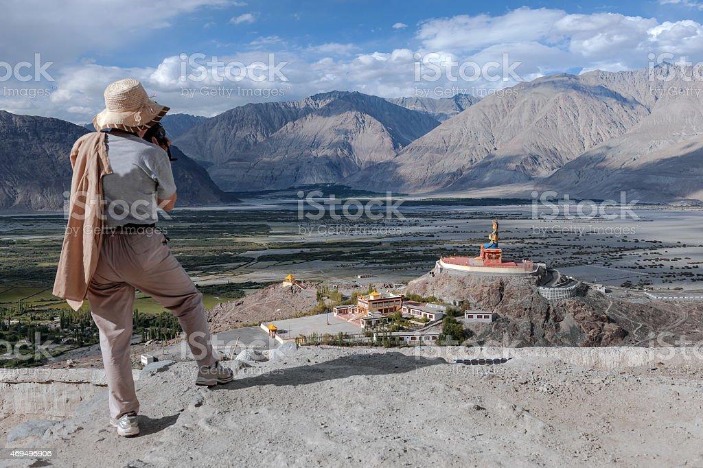 Photographer with a hat, photographs Buddhist shrine  , Stupas Nubra valley stock photo