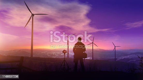 Silhouettes of wind turbines and the photographer with a tripod against the background of the sunset sky.