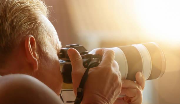 fotograaf met camara op het werk - telelens stockfoto's en -beelden