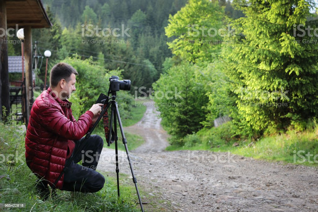 Photographer with camera on tripod shooting a landscape in forest royalty-free stock photo