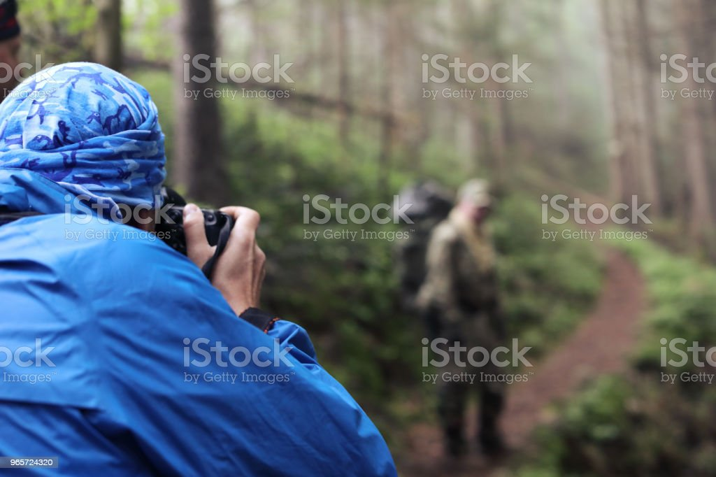 Photographer with camera on tripod shooting a landscape in forest - Royalty-free Adult Stock Photo