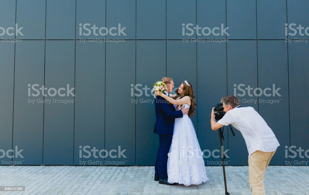 Photographer with Groom and Bride stock photo