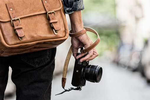 Urban man photographer with leather bag in the city. Close-up hands