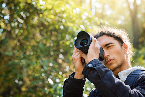 Picture with copy space of a photographer shooting pictures in forest