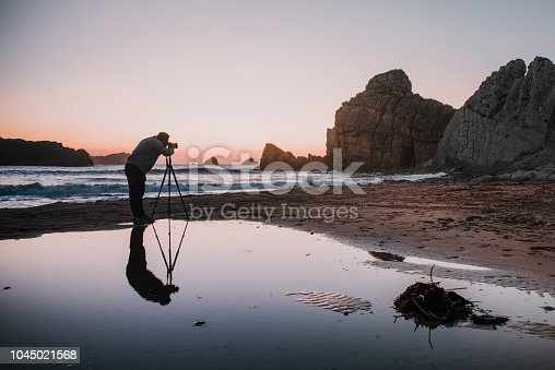 Photographer with tripod at sunset and his reflection on the water