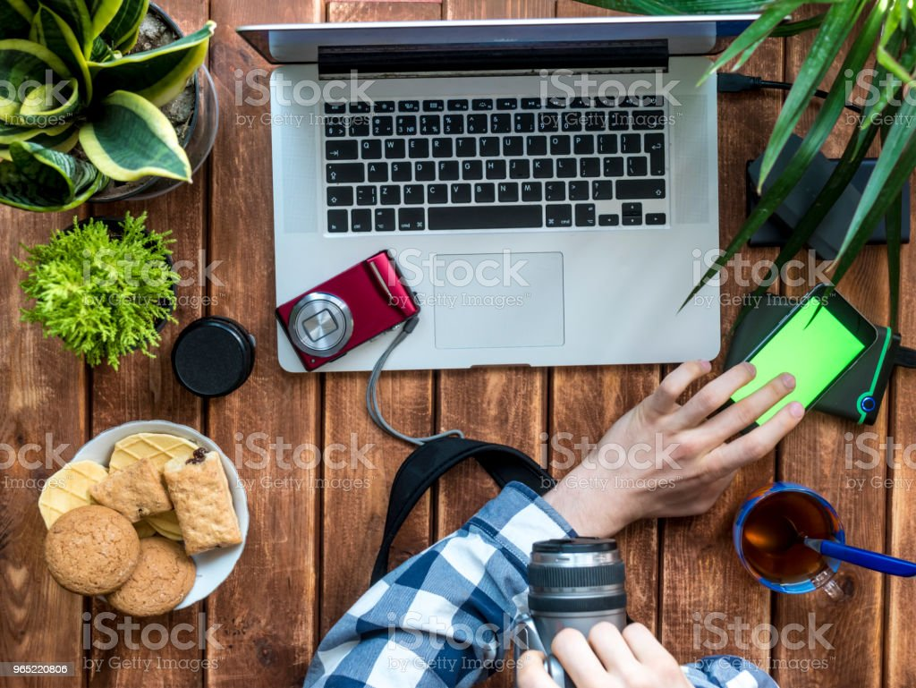 photographer working at home with camera and smartphone royalty-free stock photo