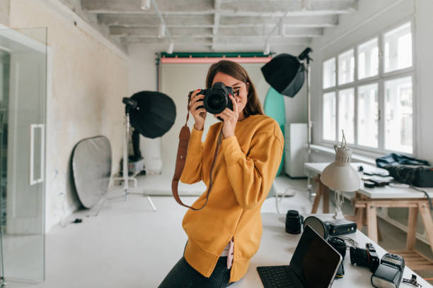 fotógrafo trabajando en un estudio - trabajo freelance fotografías e imágenes de stock