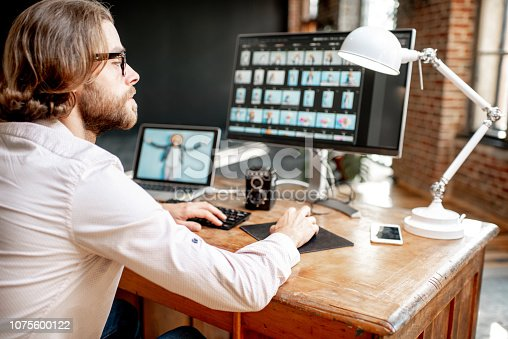 Young male photographer working with woman's portraits sitting at the working place with two computers in the studio