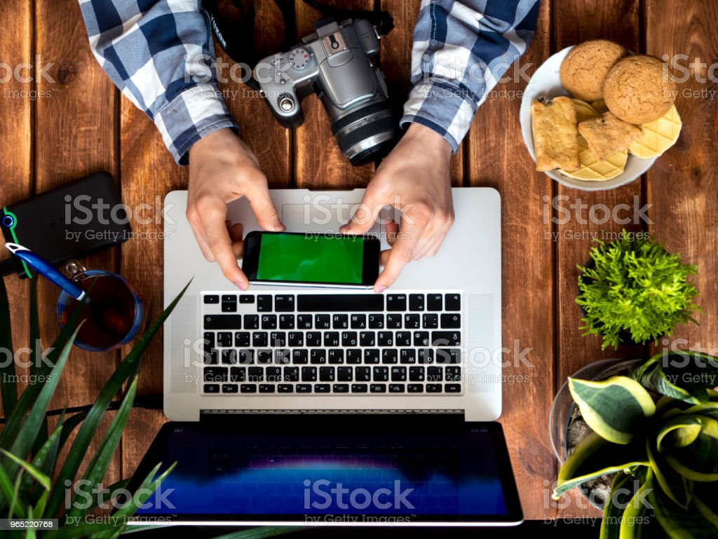photographer working using phone and laptop on a wooden table royalty-free stock photo
