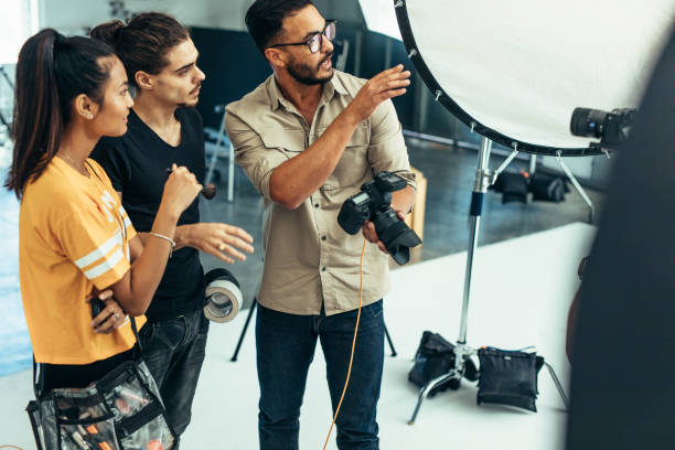 Photographer working with his team during a photo shoot in a studio Photographer explaining about the shot to his team in the studio. Photographer talking to his assistants holding a camera during a photo shoot. studio stock pictures, royalty-free photos & images