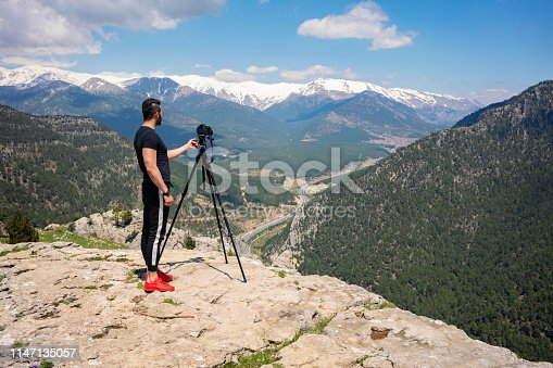 Photographer working with tripod and dslr camera on top of mountain.