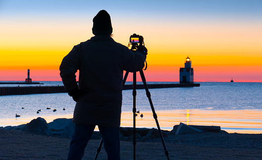 Photographer works in cold Lake Michigan March twilight.