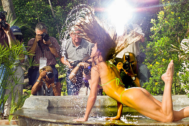 Photographers Capture the Moment With Model Delray Beach, USA - January 22, 1999:  A group of serious amateur photographers photograph a model as she throws her wet hair in the air.  They are all participating in the annual FotoFusion Workshop at the Palm Beach Photographic Centre in Delray Beach, Florida. g string bikini models stock pictures, royalty-free photos & images