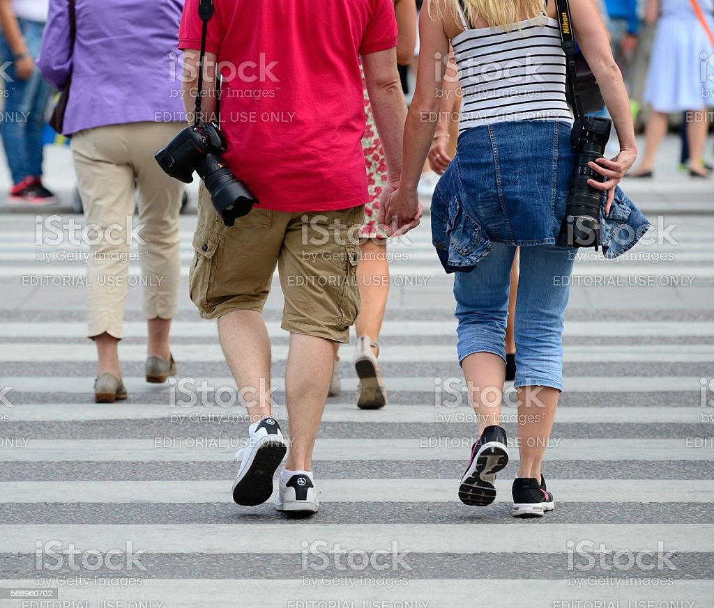 Photographers couple holding hands on street Drottninggatan, Stockholm, Sweden stock photo