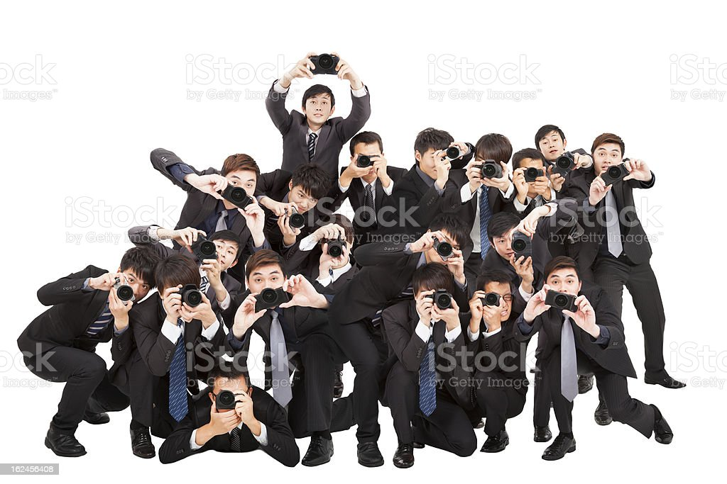 photographers holding camera pointing to you stock photo