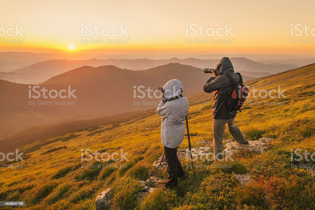 Photographers takes a sunset in the mountains stock photo