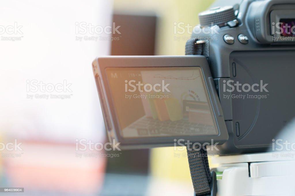 カメラの三脚の上にあるを使用してオンライン ショッピング web サイト マイクロの販売のための写真を撮る写真家 - よろい戸のロイヤリティフリーストックフォト