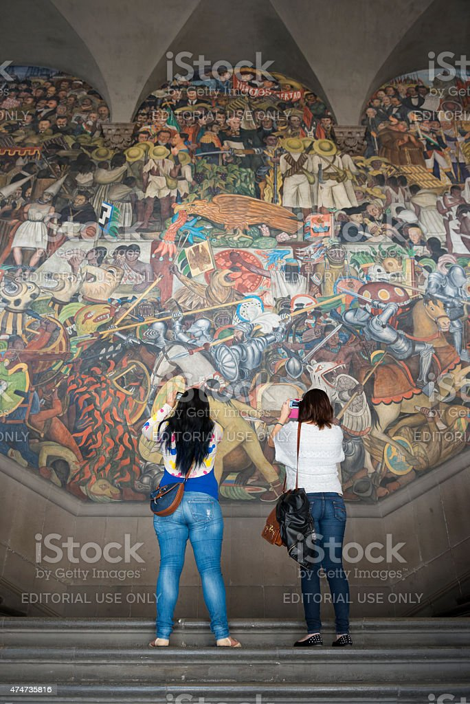 Photographing a Mexico City landmark Mexico City, Mexico - October 28, 2014: Two women stand on steps at the National Palace in Mexico City, Mexico, using their smartphones to photograph a mural by Diego Rivera, one of several painted between 1929 and 1951. The open-air murals are one of the most visited attractions in Mexico City; entrance is free. 2015 Stock Photo